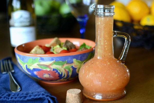 A cruet of homemade Italian vinegarette salad dressing next to a colorful salad with tomatoes and